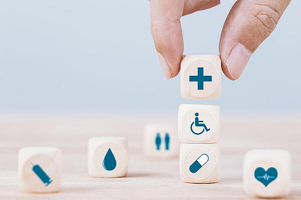 hand-chooses-emoticon-icons-healthcare-medical-symbol-wooden-block-healthcare-medical-insurance-concept_39665-204