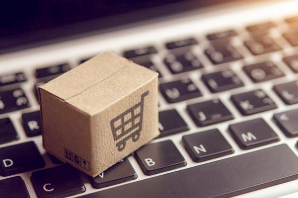 online-shopping-paper-cartons-parcel-with-shopping-cart-logo-laptop-keyboard_9635-3291