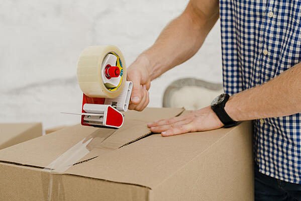 crop-man-packing-box-with-sticky-tape_23-2147758726