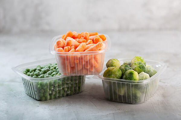 frozen-vegetables-such-as-green-peas-brussels-sprouts-baby-carrot-plastic-boxes-concrete-gray-space_118631-3209