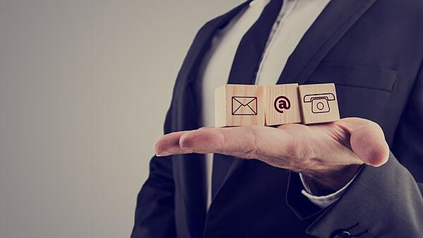 businessman-holding-three-wooden-cubes-with-contact-symbols_254268-908